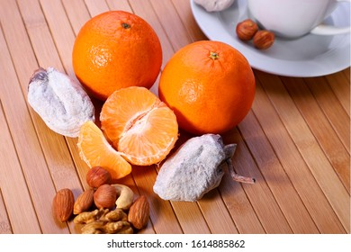 dried fruits nuts and tangerines on a wooden table