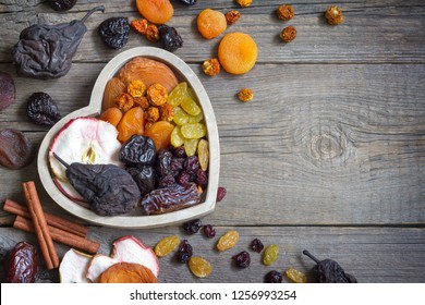 Dried fruits on wooden board in the heart food concept