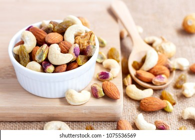 Dried fruits and variety of nuts into a bowl, a wooden spoon on the sackcloth background, such as figs, almonds, raisins, cashews, and pistachio. with copy space for your text.