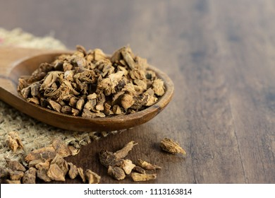 dried galangal root on a wooden spoon