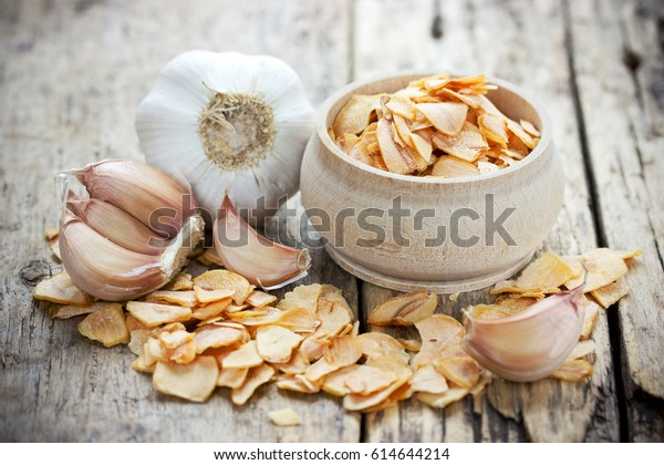 Dried garlic flakes or garlic chips and raw garlic bulb on old wooden background