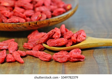 Dried goji berries in wooden spoon and plate (Lycium chinense) macro selective focus
