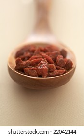 Dried goji berries in a wooden spoon