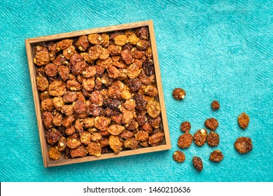 dried goldenberries  in a square wooden box against texture turquoise paper