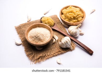 Dried granulated Garlic/Lahsun powder and paste, over moody colourful background. selective focus
