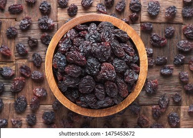 dried grapes, dark raisins in bowl on wooden table background.