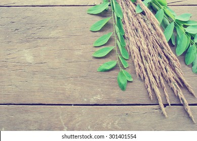 Dried grass and green leaves on rustic wooden table; can be used as background with copy-space. Image edited in faded, washed out, retro, Instagram style; nostalgic, vintage autumn concept.