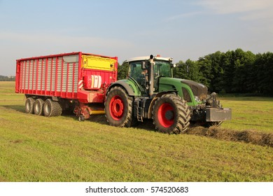 Dried grass from small mountain meadow being loaded into wagon attached to green tractor, used for feeding cows and pigs, bio agriculture, heavy machinery, frontal perspective