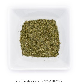 Dried green dill tips in a white bowl in top view