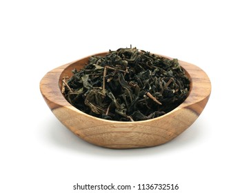 Dried green tea leaves in wooden bowl isolated on white background.