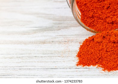 Dried ground paprika pouring out of the jar. Red spice poured on a wooden counter and free space.