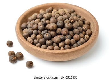 dried herb, allspice in the wooden plate. isolated on white