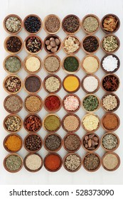 Dried herb and spice collection in wooden bowls high in antioxidants and vitamins over distressed white wood background.