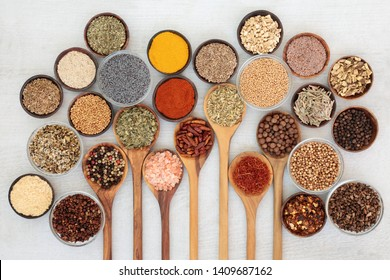 Dried herb and spice food seasoning in olive wood spoons and wooden bowls on rustic wood background.