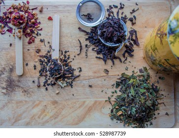 dried herbal loose tea sitting on wooden cutting board near Asian cup filling air with fragrant aroma, bringing peace, calmness, happiness and mindfulness to all that drink