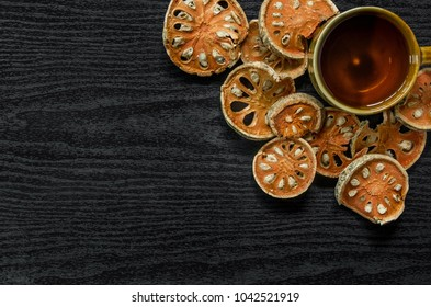 Dried herbs and dried bael fruit, Top view of bael dry and glass tea and bael juice on the wooden floor, Slices of bael fruit on the dark table.