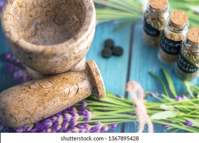 dried herbs in glass on table with mortar and pestle,  healthy living naturopathy
