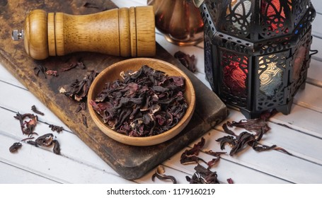 Dried hibiscus loose tea leaves in wooden bowl.