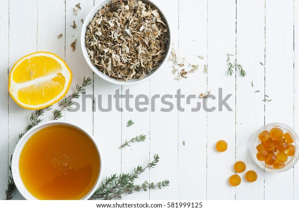 dried iceland lichen leaves, honey, lemon, thyme twigs, pills on white wood table background