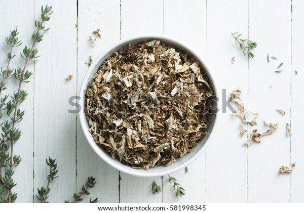 dried iceland lichen leaves and thyme twigs on white wood table background