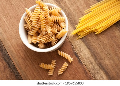 Dried Italian spiral fusilli and spaghetti pasta on a wooden kitchen table ready to be used as cooking ingredients in a Mediterranean recipe