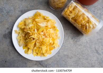 Dried jackfruit slices in white dish, Thai snack