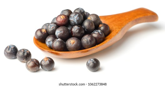 dried juniper berries in the wooden spoon, isolated on white