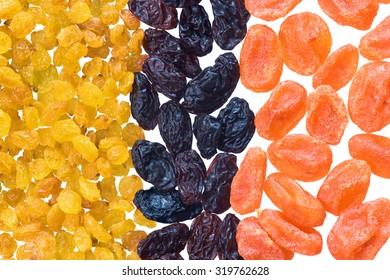 Dried kumquat, golden and black raisins isolated on white background. Vivid dried fruits.