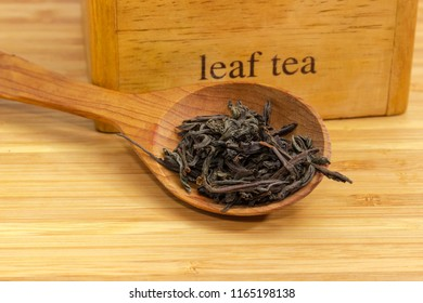 Dried large leaves of black tea in wooden spoon close-up at selective focus on a blurred background of wooden box on a bamboo surface
