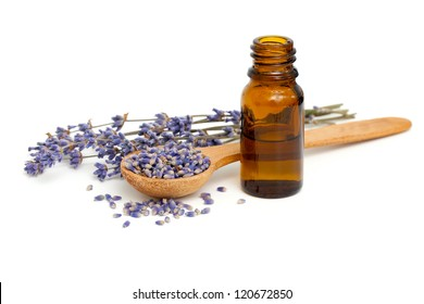 Dried lavender with a bottle of essential oil over white