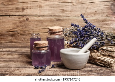 Dried lavender flowers in a in a mortar and pestle with bottle of essential lavender oil or infused water. Old books and lavender flowers bunch in the wooden background, place for text