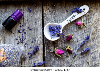 dried lavender and wild roses flowers, lavender oil and sachet with petals on wooden background