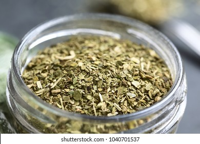 Dried leaves of yerba mate tea, a traditional tea in South-America, photographed in glass jar on slate (Selective Focus, Focus one third into the tea leaves)