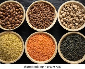 Dried, legume, leguminous plants, structure, assortment chickpea, kidney beans, pink coconut beans, green lenses, beluga lenses, millet, coral lenses, blond lenses, background. Flat lay, top view.