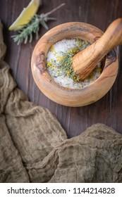 Dried Lemon & Lavender Herb in Wooden Mortar and Pestle to make Herb Salt; Fresh Sprig of Herb on Wooden Tabletop