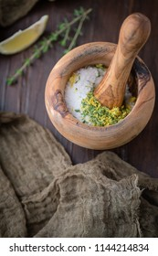 Dried Lemon & Thyme Herb in Wooden Mortar and Pestle to make Herb Salt; Fresh Sprig of Herb on Wooden Tabletop