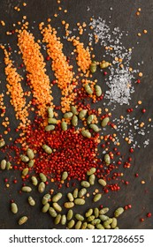 Dried lentils and soya beans  with red peppercorns and rock salt scattered on slate natural background - portrait