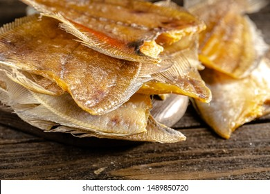 dried lumped fish, flounder with caviar, from different angles, stand and lie, at different angles, on a wooden cutting table, dark light