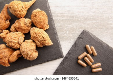 Dried maca and maca capsules on a stone plate.