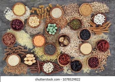 Dried macrobiotic health food with grains, cereals, pulses, nuts, seeds and whole wheat pasta. Super foods high in smart carbohydrates, protein, antioxidants and fibre on marble background top view.