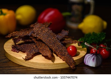 Dried meat with spices on a wooden board