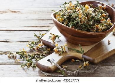 Dried medicinal herbs  in a  bowl on a wooden table.( Carqueja and Genista Tridentata).  Close-up. Alternative treatment . Selective focus