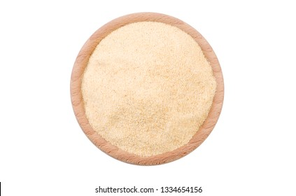 dried milled ground garlic in wooden bowl isolated on white background. Spices and food ingredients.