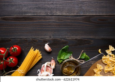 Dried mixed pasta and vegetables on the dark wooden table top view, with copy space.