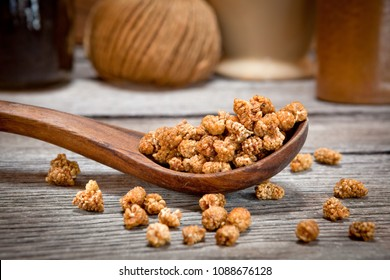 Dried mulberries in a wooden spoon