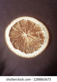 a dried orange slice on a black background