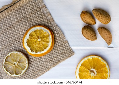 Dried oranges with almonds on the white wooden background. Decoration detail with oranges. Abstract natural still image. Toned with old fashioned sepia colors.