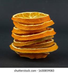 Сolumn of dried oranges on a black background
