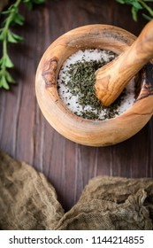 Dried Oregano Herb in Wooden Mortar and Pestle to make Herb Salt; Fresh Sprig of Herb on Wooden Tabletop
