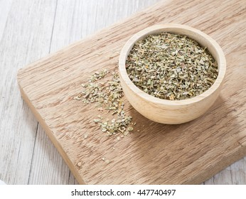 Dried oregano leaves in wooden bowl on chopping board